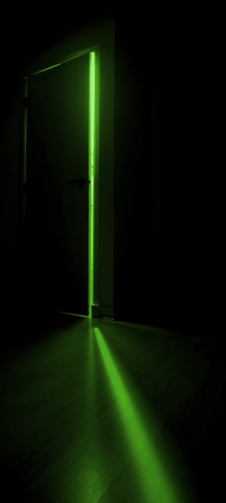 dark room leading into door with green light coming out